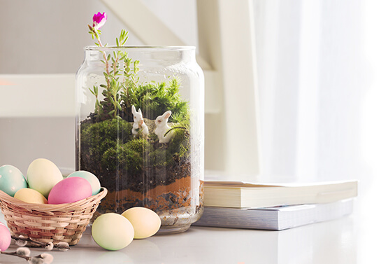 Easter decoration idea with a glass vase filled with grass and bunnies