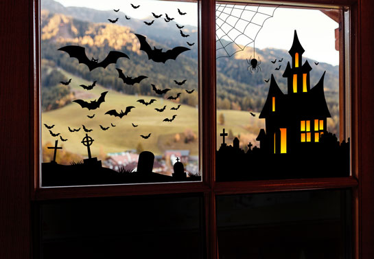 Holiday window idea for Halloween with a witch house and bats