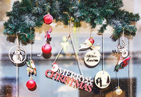 Hanging wooden decors to decorate an office window for Christmas