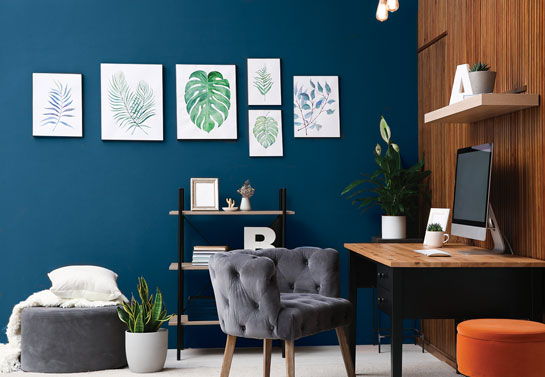 home office blue accent wall decorated with canvases