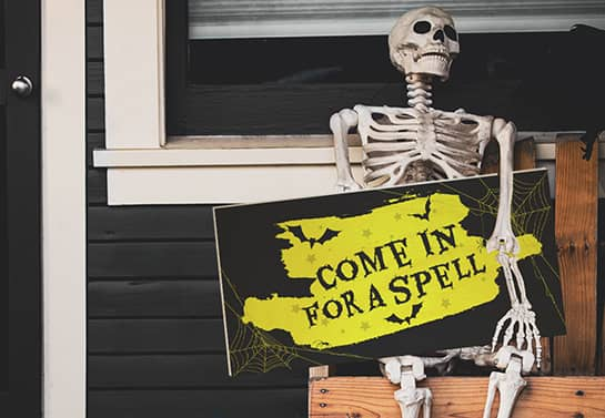 Halloween porch sign with a creepy message put in a skeleton's hand