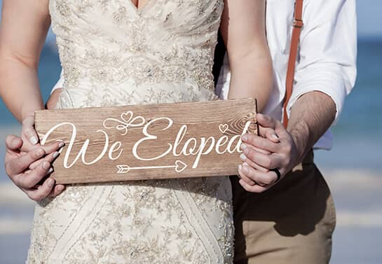 wedding sign idea with the text We Eloped in the hands of a couple
