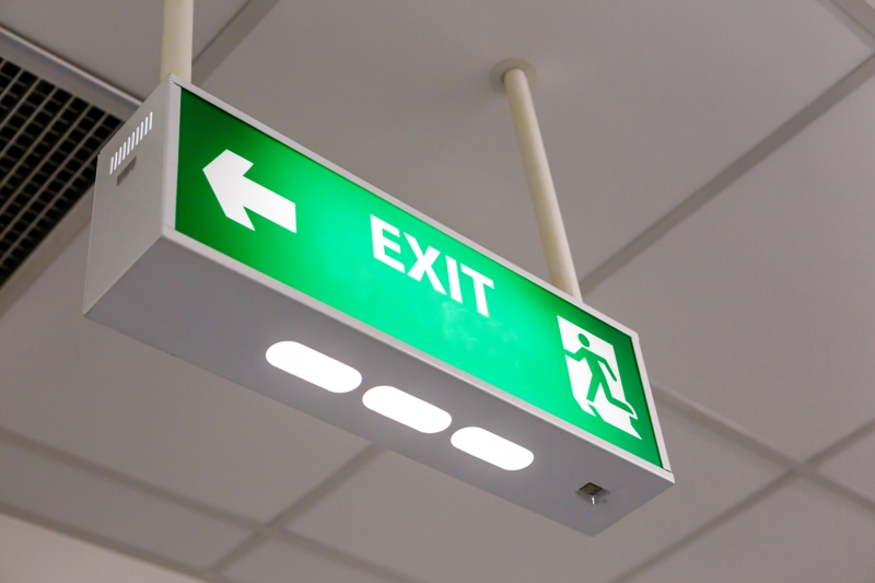 example of an emergency exit signage in green color hanging from the ceiling with a directional arrow