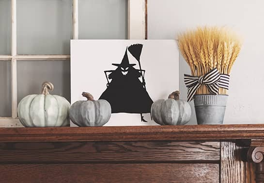 witch-themed Halloween mantel sign with grey decorative pumpkins