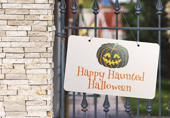 Happy Haunted Halloween hanging sign displayed on the fence