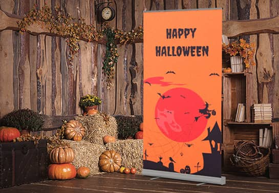 indoor Halloween party backdrop in orange displaying a witch house