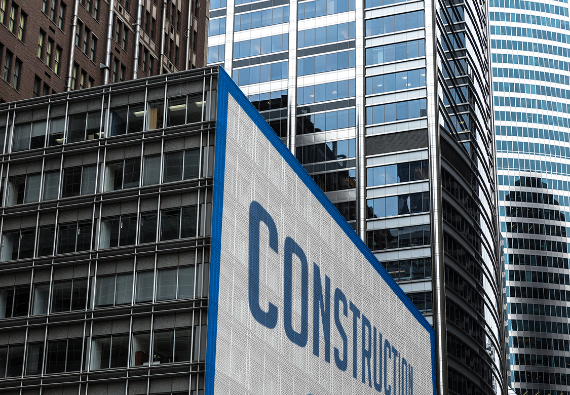 example of a mesh banner printed in large format with the word Construction fixed to a building wall