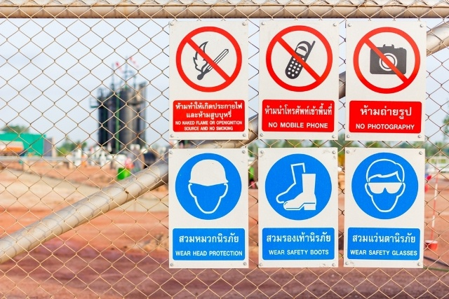 examples of safety signs with different warning notes fixed to a fence for keeping industrial facility safety