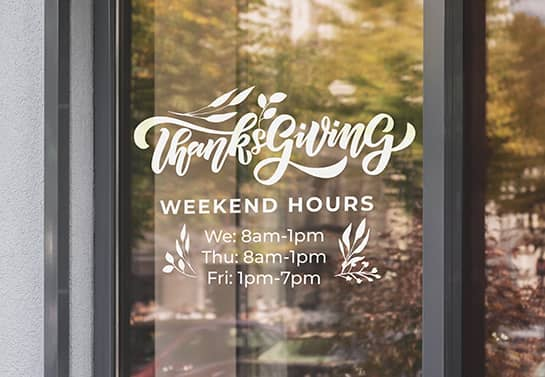 Thanksgiving business hours sign in white displayed on the door