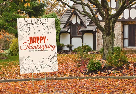 beige Thanksgiving yard sign surrounded by autumn leaves