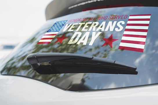 Veterans Day car sign with patriotic symbols displayed on the rear window