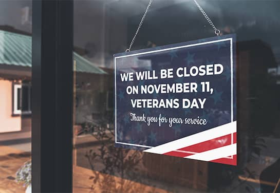 hanging Veterans Day closed sign in blue, red and white colors