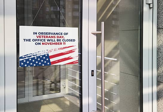 hanging office closed sign for Veterans Day displaying the US flag