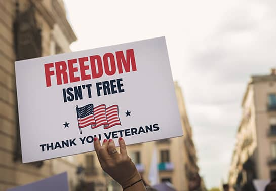 Veterans Day parade sign displaying a freedom quote