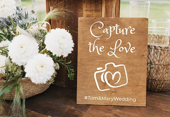 wooden wedding sign idea with a hashtag and camera icon