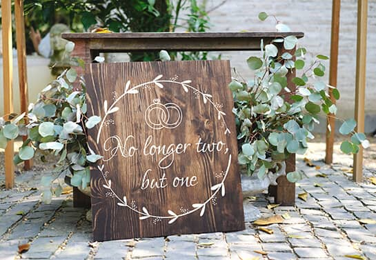 wooden wedding welcome sign idea with a quote and thematic elements